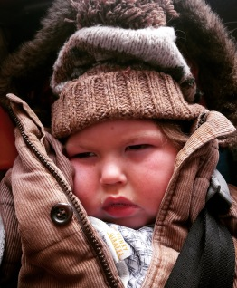 Portrait of a three-year-old boy squashed into a brown corduroy coat and woolly bobble hat, looking grumpy